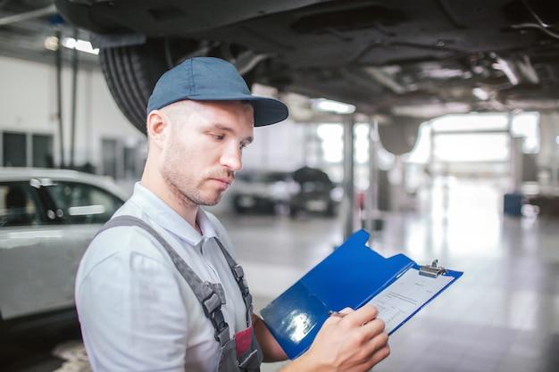 Bild des arbeiters, der in der garage steht. er meint es ernst. guy hält eine plastikmappe mit papieren in der hand und seufzt sie. mann trägt graue uniform und mütze. Premium Fotos