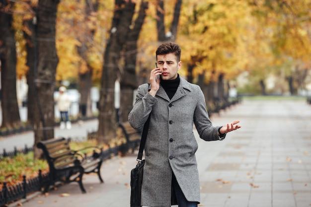Bild des eleganten mannes im mantel mit tasche gehend in stadtpark und auf smartphone im herbst sprechend Kostenlose Fotos