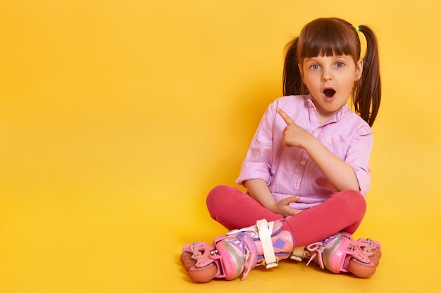 Bild des erstaunten weiblichen kindes mit weit geöffnetem mund, der auf boden sitzt Kostenlose Fotos