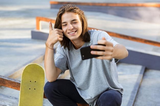 Bild des fröhlichen jungen skater-kerls sitzen im park mit skateboard nehmen selfie per handy mit daumen hoch. Premium Fotos