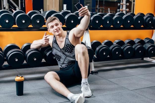 Bild des glücklichen jungen sportlers, der in der turnhalle sitzt und machen selfie. Premium Fotos
