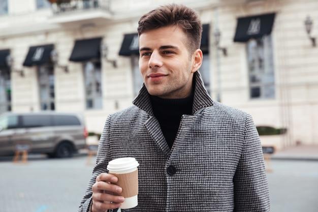 Bild des gutaussehenden mannes mitnehmerkaffee von der papierschale genießend, beim gehen hinunter leere straße Kostenlose Fotos