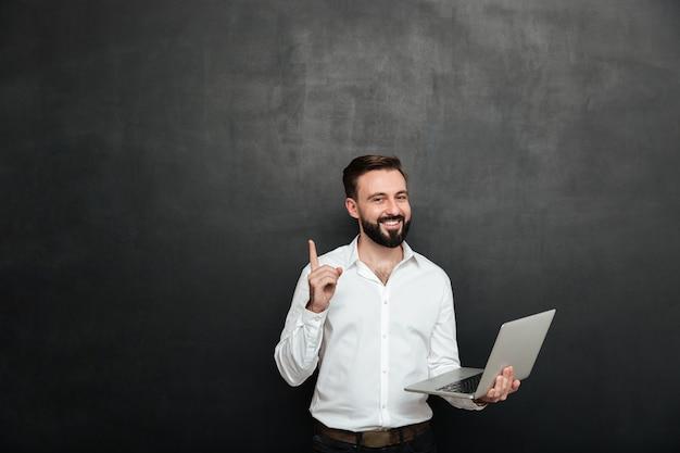 Bild des intelligenten brunettemannes, der im büro unter verwendung des silbernen laptops oben gestikuliert mit dem finger, lokalisiert über dunkelgrauer wand arbeitet Kostenlose Fotos
