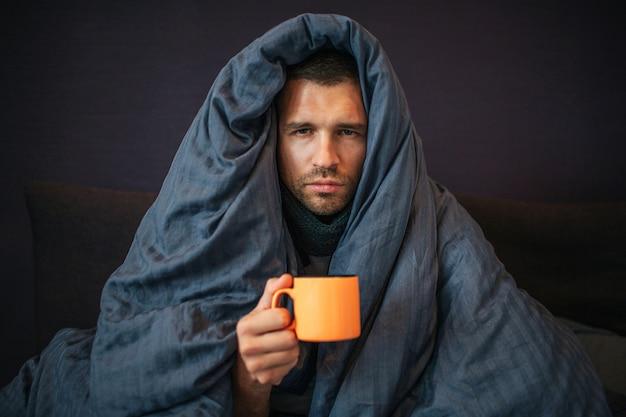 Bild des jungen mannes sitzt auf dem bett und bedeckt mit dunkelblauer decke. er hält eine orangefarbene tasse tee. guy schaut vor die kamera. er meint es ernst. junger mann ist emotionslos. Premium Fotos