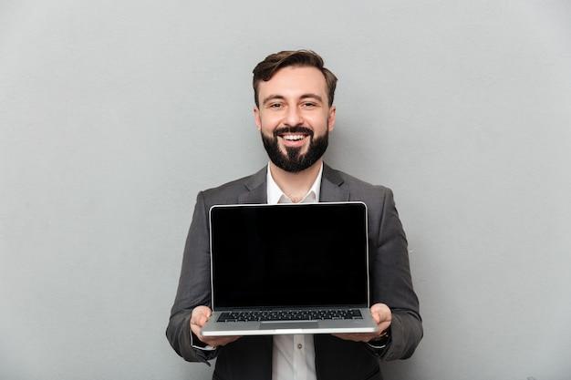 Bild des lächelnden bärtigen mannes silbernen personal-computer halten, der schwarzen schirm zeigt und auf der kamera, lokalisiert über grauer wand schaut Kostenlose Fotos