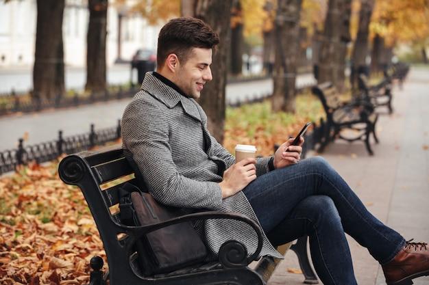 Bild des lächelnden brunettemannes im mantel und in jeans mitnehmerkaffee trinkend und seinen handy verwendend, beim sitzen auf bank im park Kostenlose Fotos