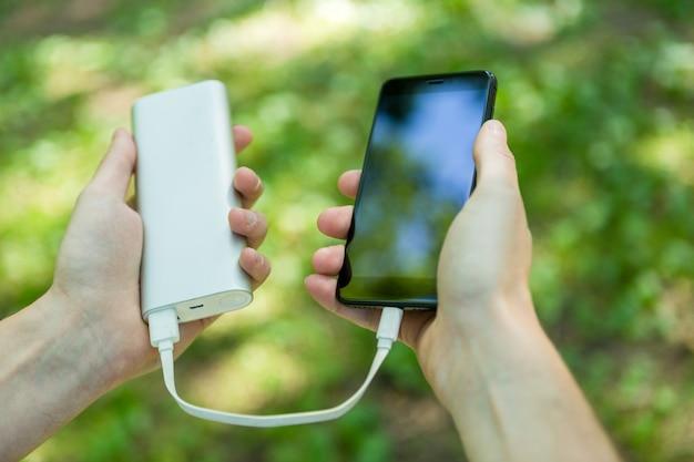 Bild des mannes telefon und powerbank halten Premium Fotos