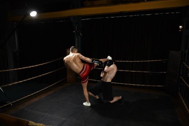 Bild des muskulösen athletischen jungen mannes, der hemdlos innerhalb des boxrings steht und unerkennbaren männlichen gegner in sein gesicht tritt. konzept für menschen, sport, entschlossenheit, wettbewerb und rivalität Kostenlose Fotos