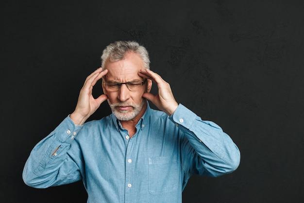Bild des reifen mannes 60s mit grauem haar und bart, der unter migräne leidet und schläfen aufgrund von kopfschmerzen reibt, isoliert über schwarzer wand Premium Fotos