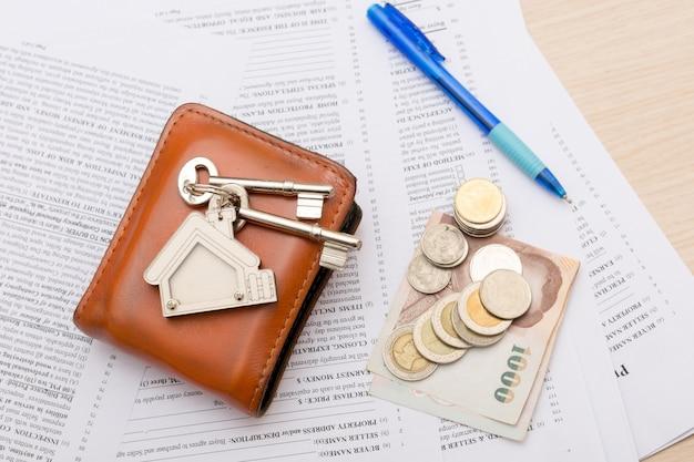 Bild des wohnmietvertrags mit geld und schlüsseln. unterzeichneter vertrag und schlüssel des eigentums mit dokumenten. konzept für das immobiliengeschäft. Premium Fotos