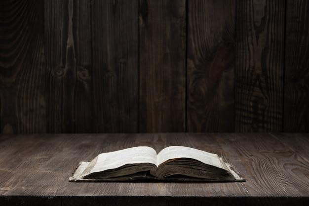 Bild einer alten heiligen bibel auf hölzernem hintergrund auf hölzernem hintergrund in einem dunklen raum Premium Fotos