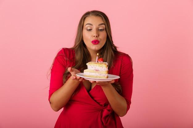 Bild einer glücklichen jungen frau lokalisiert über rosa wand, die kuchen hält. Premium Fotos