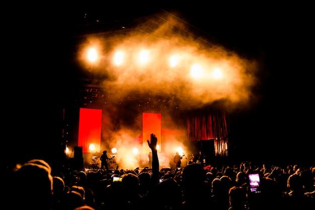 Bild einer menge leute, die nachtaufführung genießen, große unerkennbare menge, die mit erhobenen händen und handys auf konzert tanzt. nachtleben Premium Fotos