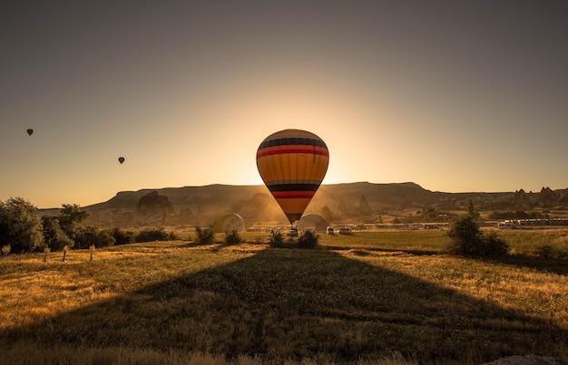 Bild eines bunten heißluftballons in einem feld, das durch grün und berge während sonnenuntergang umgeben ist Kostenlose Fotos