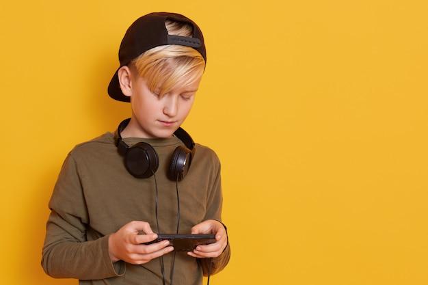 Bild eines jungen mit kopfhörern um den hals, kleiner kerl, der wacholdergrünhemd und schwarze hintere visierkappe trägt Kostenlose Fotos