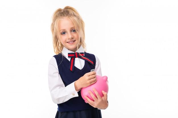Bild eines kleinen mädchens mit blonden haaren hält rosa schwein sparbüchse und lächelt Premium Fotos