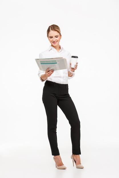 Bild in voller länge der fröhlichen blonden geschäftsfrau, die zeitung liest, während tasse kaffee über weißer wand hält Kostenlose Fotos