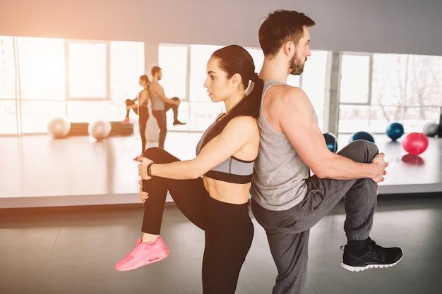 Bild von mann und frau, die rücken an rücken stehen und ein bein hochziehen. sie versuchen, das gleichgewicht der körper auf der einen seite zu halten. Premium Fotos