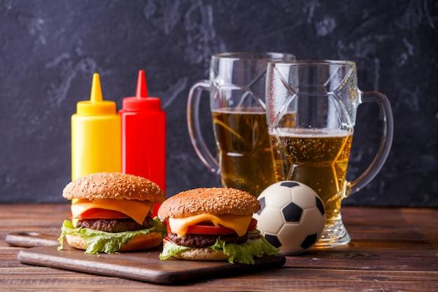 Bild von zwei hamburgern, gläser, fußball, ketschup Premium Fotos