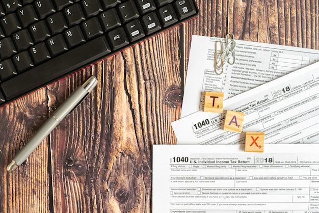 Bilden sie 1040 von amerikanischen steuern auf dem schreibtisch eines steuerzahlers. Premium Fotos