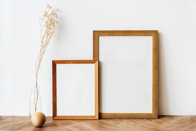 Bilderrahmen auf einem hölzernen sideboard-tisch mit getrockneten blumen Kostenlose Fotos