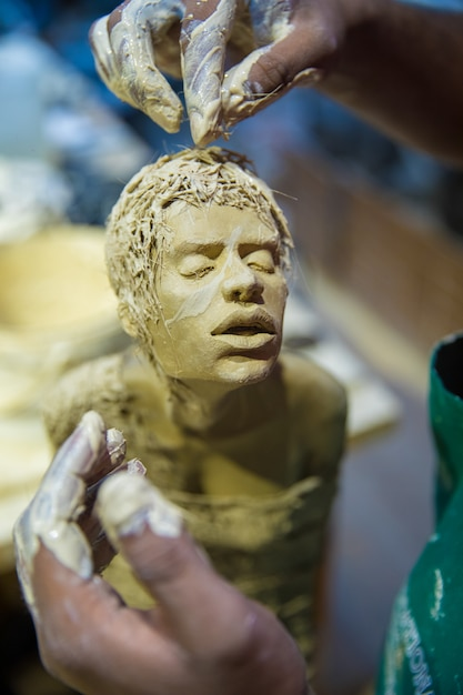Bildhauer, der menschliches körpermodell mit ton macht Kostenlose Fotos