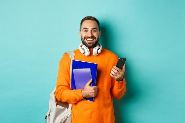 Bildung. hübscher männlicher student mit kopfhörern und rucksack, mit smartphone Kostenlose Fotos