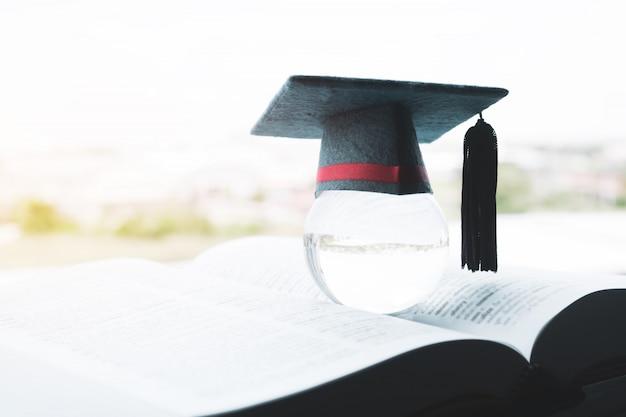 Bildung in globalem, abschlusskappe auf spitzenglaskugel auf lehrbuch Premium Fotos