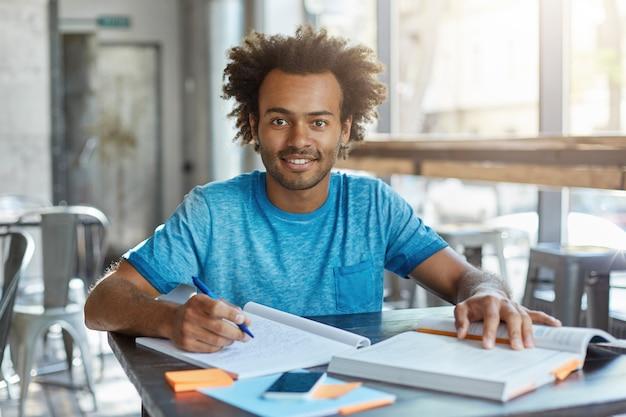 Bildung und wissen, menschen und lebensstil. innenporträt des fröhlichen dunkelhäutigen studenten, der hausaufgabe auf mathe macht, im café arbeitet, notizen vom lehrbuch notiert Kostenlose Fotos