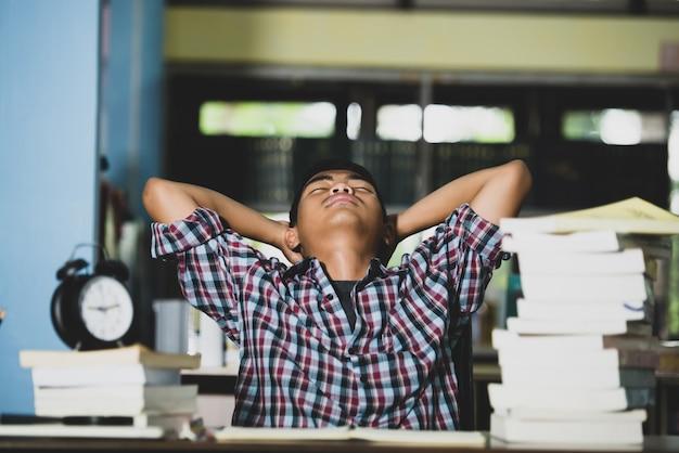 Bildungskonzept: müder student in einer bibliothek Kostenlose Fotos