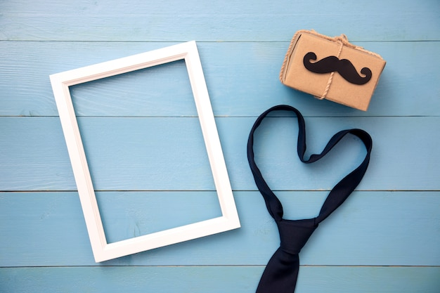 Bindung, geschenkbox, papierschnurrbart, fotorahmen auf hölzernem hintergrund mit kopienraum. alles gute zum vatertag. Premium Fotos