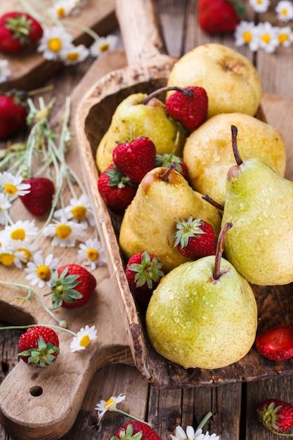 Birnen, erdbeeren und gänseblümchen, stillleben Premium Fotos