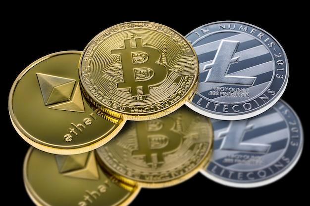 Bitcoin-, äthereum- und litecoinmünzen getrennt auf schwarzem mit reflexion. Premium Fotos