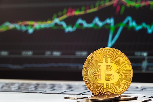 Bitcoin btc-kryptowährungen mit der anzeige von tradining-graph-laptops im hintergrund. Premium Fotos