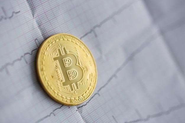 Bitcoin lebt. die goldmünze liegt auf einem papier Premium Fotos