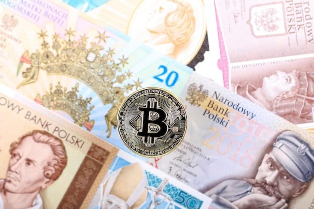 Bitcoin-münze auf dem hintergrund von polnischen banknoten Premium Fotos