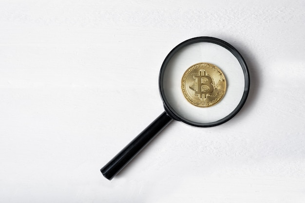 Bitcoin-münze durch ein vergrößerungsglas auf einem weißen hintergrund Premium Fotos