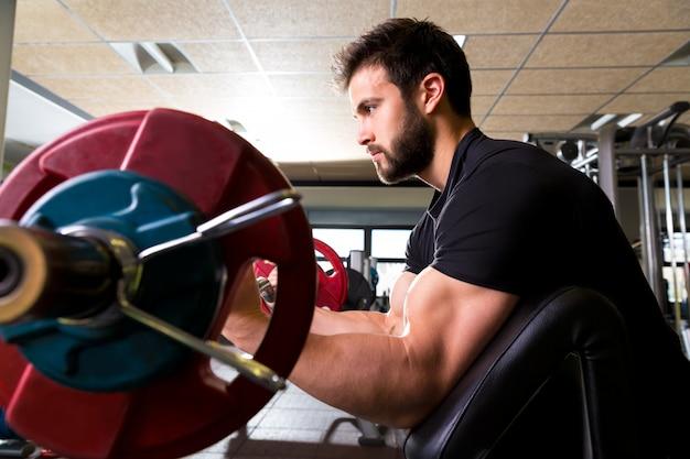 Bizeps-prediger bank arm curl training mann im fitnessstudio Premium Fotos