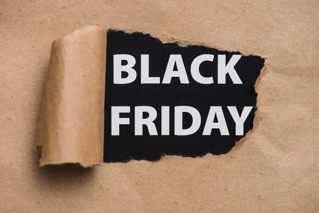 Black friday-inschrift, die durch handwerksblatt schaut Kostenlose Fotos
