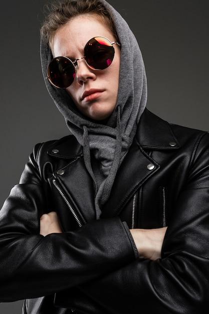 Black friday konzept. attraktives stilvolles kaukasisches mädchen in einer schwarzen lederjacke und einem grauen sweatshirt und einer sonnenbrille auf einem dunkelgrauen hintergrund Premium Fotos