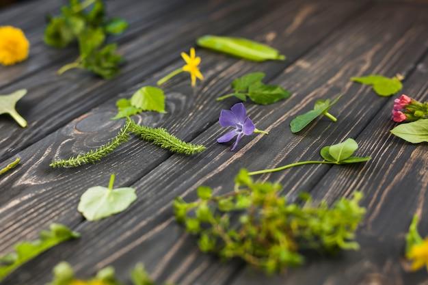 Blätter und blumen auf hölzernem strukturiertem hintergrund Kostenlose Fotos