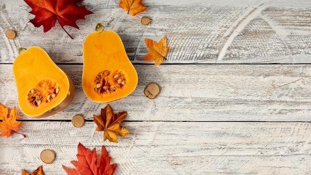 Blätter und halbierter kürbis auf weißem hölzernem hintergrund Kostenlose Fotos