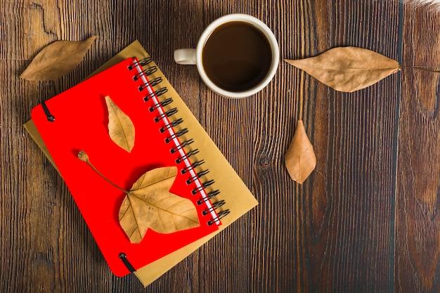 Blätter und kaffee in der nähe von notizblöcken ...