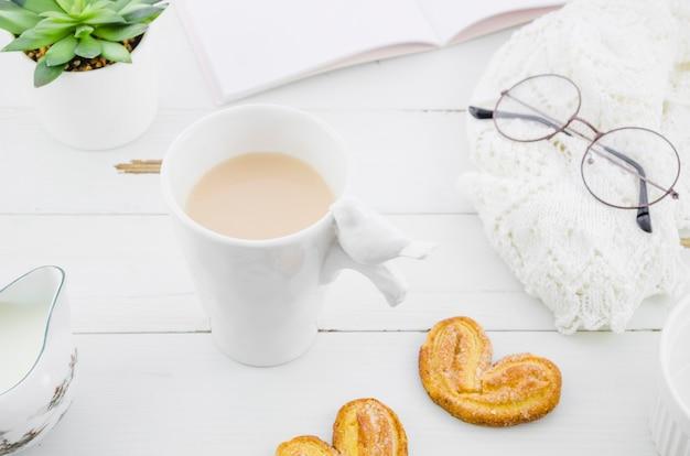 Blätterteigplätzchen palmiers mit weißer teeschale des porzellans auf hölzernem schreibtisch Kostenlose Fotos