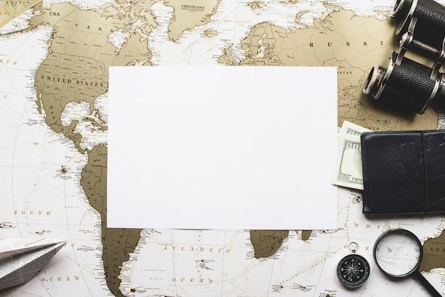 Blank papier mit reiseutensilien und weltkarte hintergrund Kostenlose Fotos