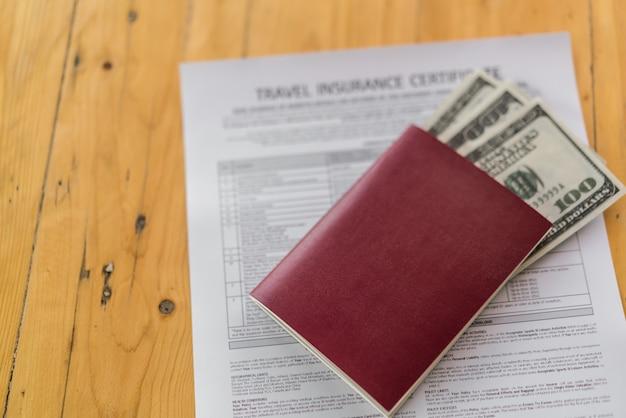 Blank pass mit us-dollar auf holztisch über travel aviation insurance antragsformular. Kostenlose Fotos