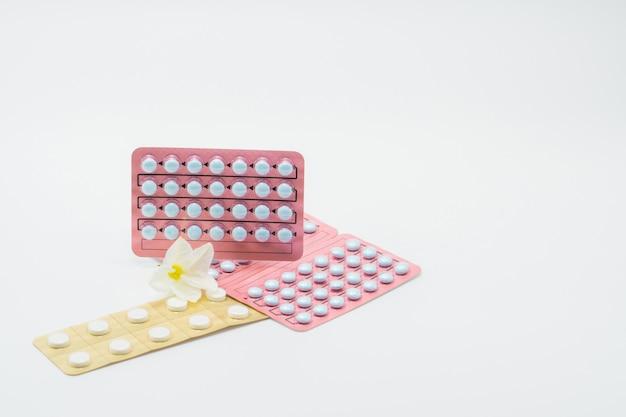 Blasenverpackung von hormonen für frauen und blume der wechseljahre der behandlung auf weißem hintergrund. hormonersatztherapie. cyproteronacetat: steroidale antiandrogene bei fortgeschrittenem prostatakrebs. Premium Fotos