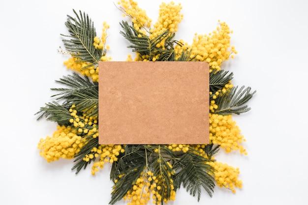 Blatt des leeren papiers auf gelben blumenniederlassungen Kostenlose Fotos