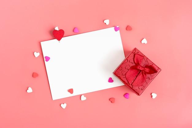 Blatt papier für nachricht, roter umschlag, geschenkbox, süßigkeiten in form von herzen. fröhlichen valentinstag Premium Fotos