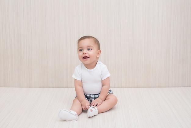 Blauäugiges baby auf weißem hölzernem hintergrund Premium Fotos